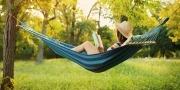 Vrouw leest een boek in een hangmat in de tuin
