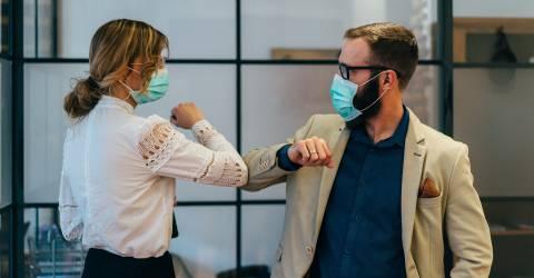 Zakenmensen groeten elkaar tijdens COVID-19 pandemie