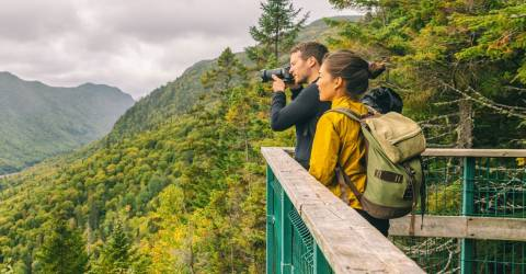 Een man en een vrouw maken foto's in de bergen op vakantie
